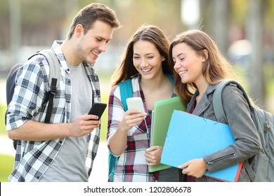 Three happy students watching media content in their smart phones in a park