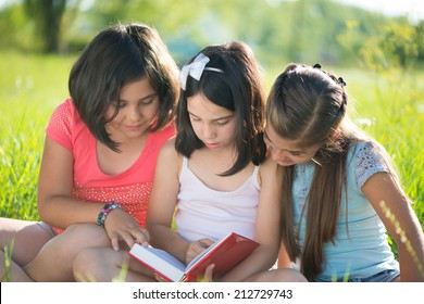 Three happy teen girls reading book at park