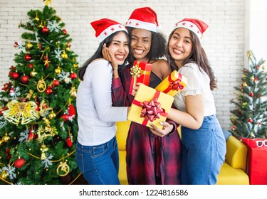 Three happy woman having a Christmas present in the Christmas party. Christmas and New Year concept.