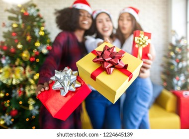 Three happy women giving you a Christmas present in the Christmas party. Christmas and New Year concept.