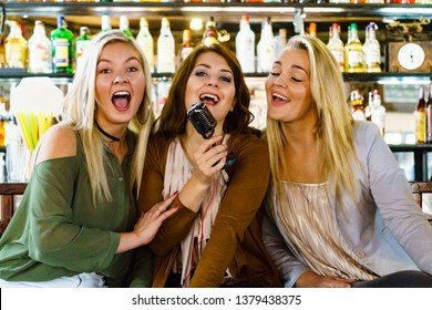 Three happy women having girls night out in pub, enjoying free time in karaoke bar sitting together holding old fashioned vintage microphone