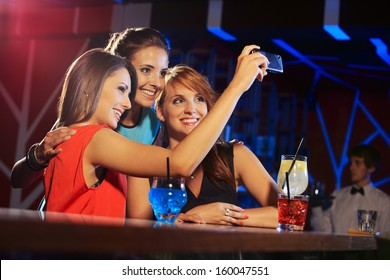Three happy women at an nightclub party taking a self-portrait