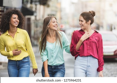 Three happy women walking in the city, talking each other and smiling
