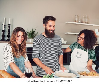 Three happy young adult diverse male and friends having a cooking party indoors. Bread and ingredients on table in front of them.