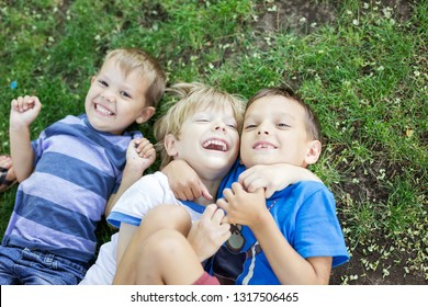 Three happy young boys in summer park. Friends or siblings hugging and laughing while lying down on green grass.