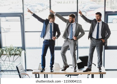 three happy young businessmen dancing on table in office