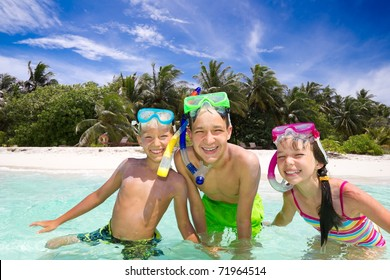 Three happy young children with snorkels playing in sea, tropical beach in background.