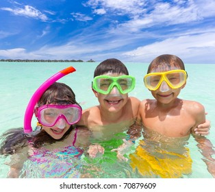 Three happy young children in tropical sea with snorkels and face masks, blue sky and cloudscape background.
