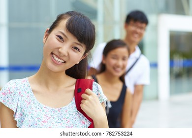 three happy young Chinese or asian college students looking at camera smile