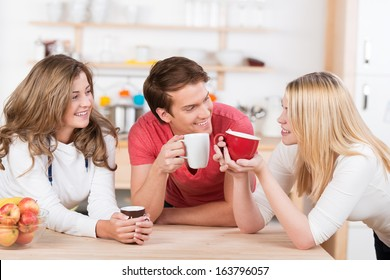 Three happy young college students having coffee together in the kitchen laugh and smile as they group around the wooden counter