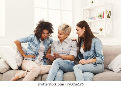 Three happy young female friends talking at home, chatting about manicure and beauty, gossip and slumber party concept, copy space