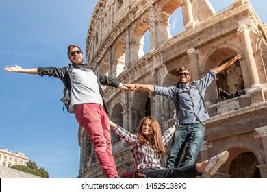 Drei glückliche junge Freunde Touristen stehen vor dem Kolosseum in Rome posium für Bilder mit Spaß
