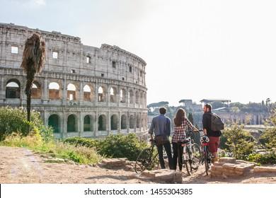 Drei glückliche junge Freunde, die im Kolosseum in Rom mit Fahrrädern reisen und Spaß haben