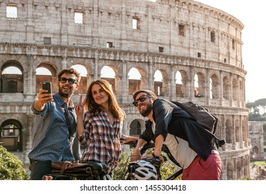 Drei fröhliche junge Freunde Touristen mit Fahrrädern im Kolosseum in Rom, die mit Smartphone fotografieren und sich selben