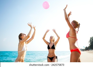 Three happy young girlfriends playing volleyball at the tropical beach, unfocused