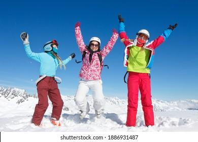 Trois jeunes filles heureuses en vacances d'hiver dans les montagnes saute dans la neige