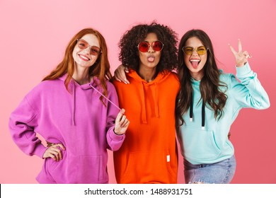 Three happy young girls wearing colorful hoodies standing isolated over pink background, looking at camera