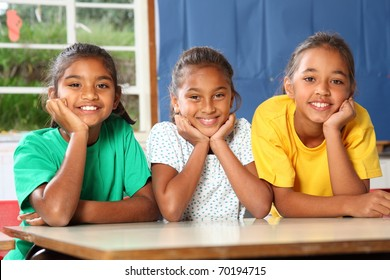 Three happy young school girls leaning on desk in class