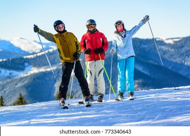 Three happy young skiers having fun on winter ski slope high in the winter mountains