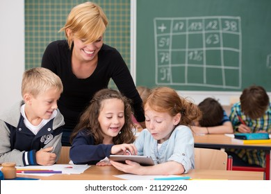Three happy young students using a tablet in class exclaiming in awe at the information on the screen watched by a smiling female teacher
