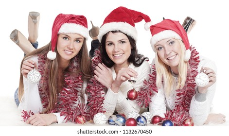 three happy young women in costumes of Santa Claus