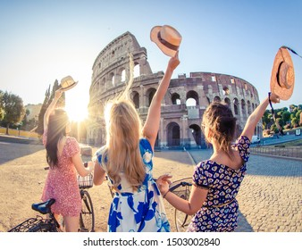 Three happy young women friends tourists with bikes waving hats at Colosseum in Rome, Italy at sunrise.