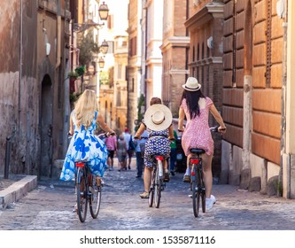 Drei glückliche junge Frauen Freunde Touristen mit Fahrrädern in typischen Gassen in Rom, Italien bei Sonnenaufgang.