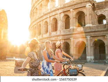 Three happy young women friends tourists with bikes at Colosseum in Rome, Italy at sunrise.