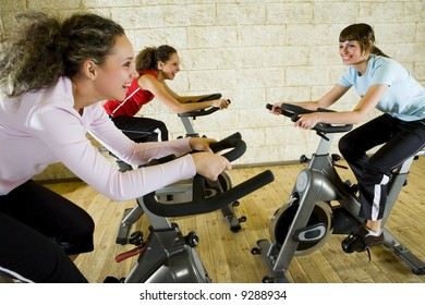 Three happy, young women working out on exercise bicycle at the gym. Side view.