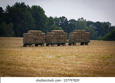 Three hay wagons stacked with hay bales