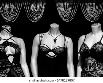 Three headless Caucasian female mannequins wearing lingerie beneath four festoons of fake diamond necklaces in a shop window in strong sunlight, in black and white, with digital painting effect