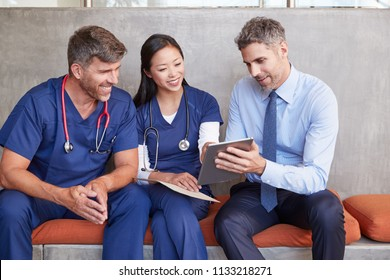 Three healthcare workers sit using tablet computer together