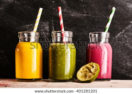 Three healthy fresh fruit and vegetable smoothies, with mango, kale and raspberry, blended with yogurt and served in small mason jars on a rustic table