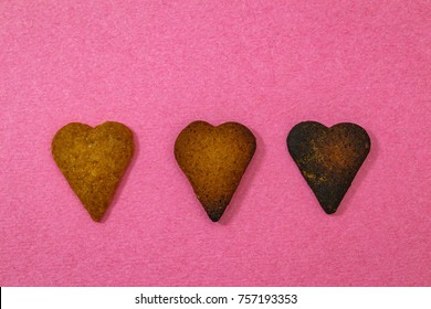 Three heart shaped  cookies, burnt and edible on pink colored baking paper background