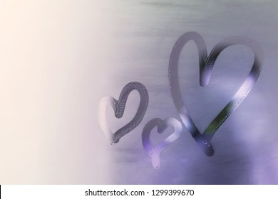 Three hearts is painted on the misted glass