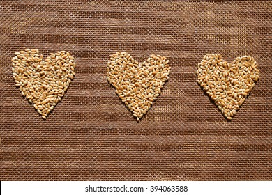 Three hearts from wheat grains drawn on brown burlap