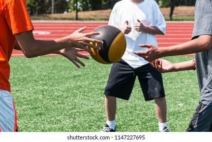 Three high school athletes are twisting sideways throwing a medicine ball to each other during strength pratice.