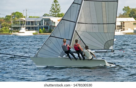 Three high school children sailing racing at speed in a high school championship regatta. Teamwork by junior sailors racing on saltwater Lake Macquarie. Photo for commercial use.