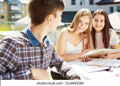 three high school students. students friends learn, do homework together, spend time in outdoor. The guy student on the foreground, focus on the girl