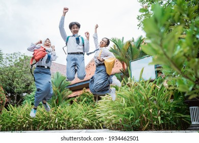 three high school students jumping high wearing school bags raising their hands together