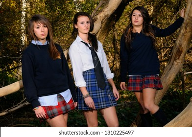 Three highschool girls in private school uniforms hanging out in a thick forest