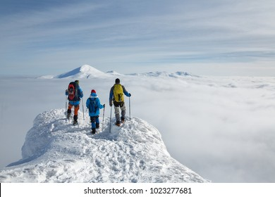 Three hikers with backpacks are on a high snow-covered peak above the clouds in the mountains. They rest after a heavy ascent, enjoying an incredible view.