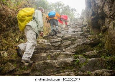 Three hikers on the Inca trail, in the rain and fog near the Puyupatamarca archological site, Peru.  Many of the stones in the trail were hand carved by ancient peruvians.