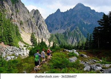 Three Hikers on Mountain Trail in Cascade Mountains.   North Cascades, Washington