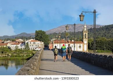 Three hikers on their backs crossing a Roman bridge. Ponte de Lima, Portugal