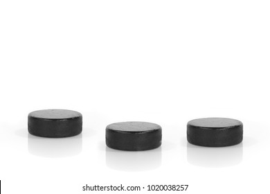 Three hockey pucks on a white background. Texture, background, concept
