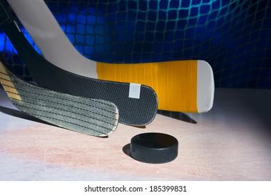 Three hockey sticks on faceoff spot.