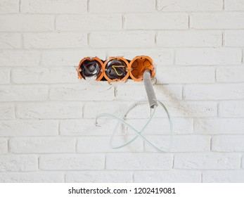 three holes in the wall with electrical wires to connect sockets