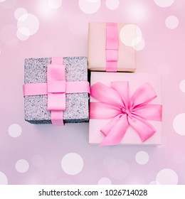 Three holiday gift boxes tied with satin ribbon on pink background. Festive glare lights. The view from the top