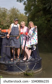 Three holidaymakers traveling on a narrowboat early morning. Holding mugs and women wearing dressing gowns